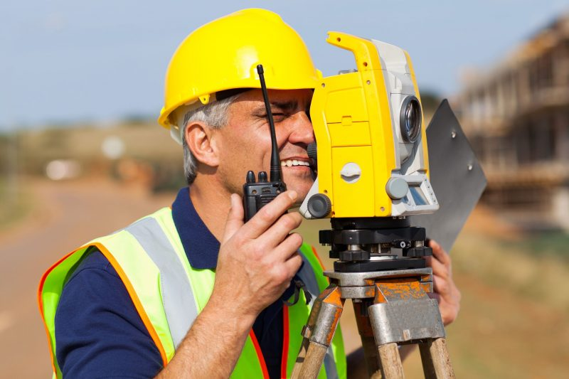 senior land surveyor working with tacheometer on construction site